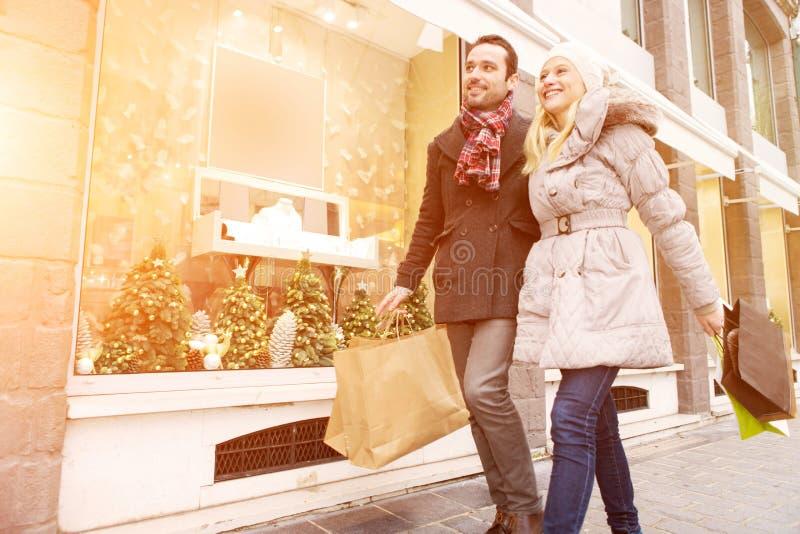 Jong aantrekkelijk paar die wat venster het winkelen doen stock foto