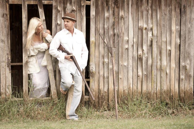 Jong aantrekkelijk paar die zich tegen houten schuurmuur verenigen stock afbeeldingen