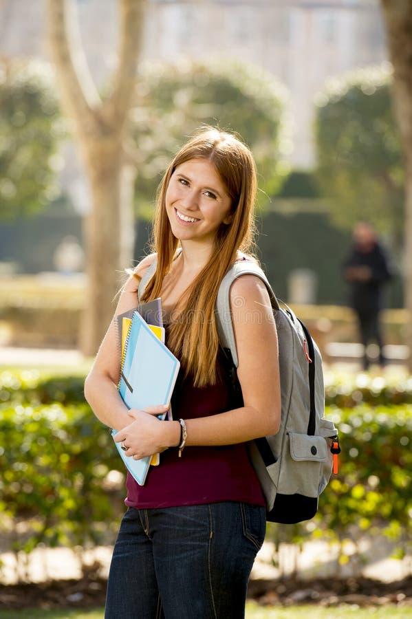 Jong aantrekkelijk studentenmeisje in de universitaire dragende boeken en de rugzak van het campus groene park stock afbeelding