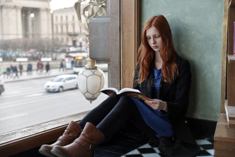 Jong aantrekkelijk vrouwelijk studentenmeisje met boek in handen het zitten stock afbeelding
