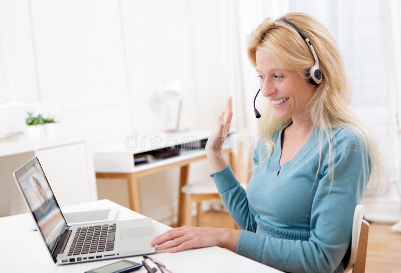 Jong aantrekkelijk vrouwenblonde die op laptop babbelen stock foto