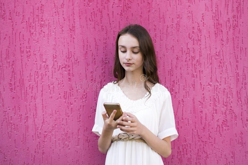 Jong aantrekkelijk wijfje die mobiele telefoon met behulp van stock foto's