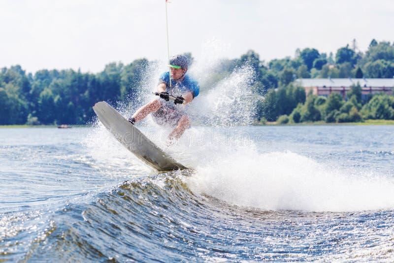 Jong actief personenvervoer wakeboard op een golf van een motorboot op de zomermeer royalty-vrije stock foto