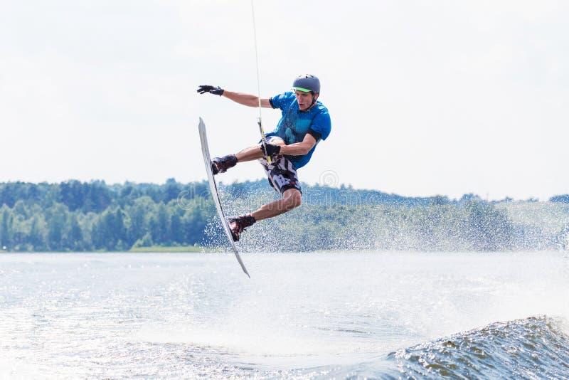 Jong actief personenvervoer wakeboard op een golf van een motorboot op de zomermeer royalty-vrije stock fotografie