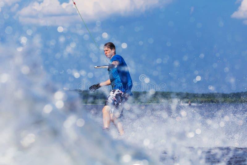 Jong actief personenvervoer wakeboard op een golf van een motorboot op de zomermeer stock afbeeldingen