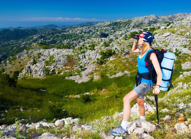 Het wijfje in bergen kijkt in binoculair stock foto's