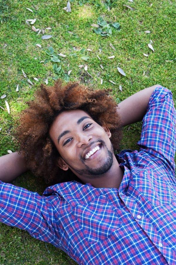 Jong Afrikaans Amerikaans mannetje dat in gras ligt stock afbeeldingen