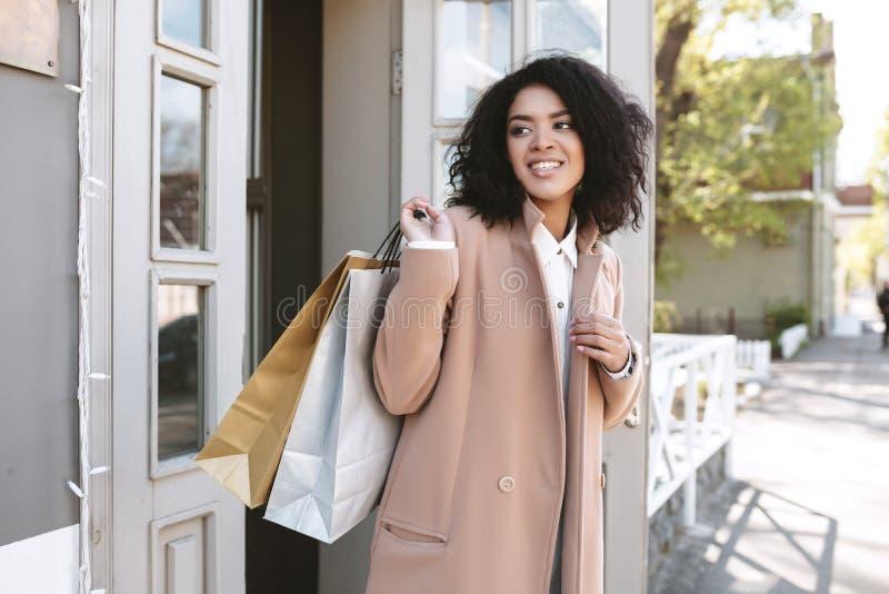 Jong Afrikaans Amerikaans meisje met donker krullend haar die zich dichtbij het deurportret bevinden van mooie dame met het winke stock afbeeldingen