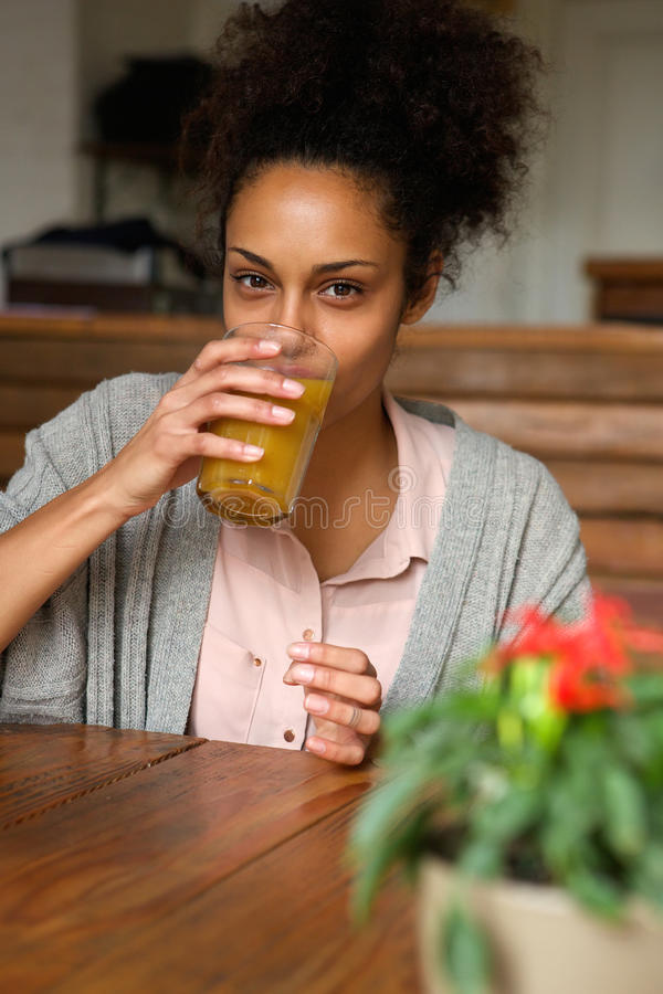 Jong Afrikaans Amerikaans vrouw het drinken jus d'orange stock afbeelding