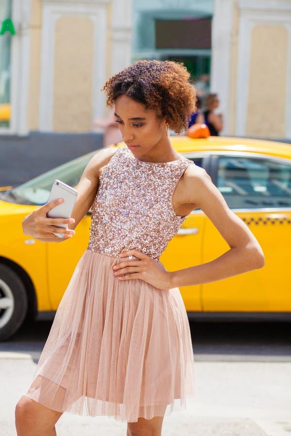 Jong Afrikaans Amerikaans zwarte in roze kleding die op cellphone spreken royalty-vrije stock foto