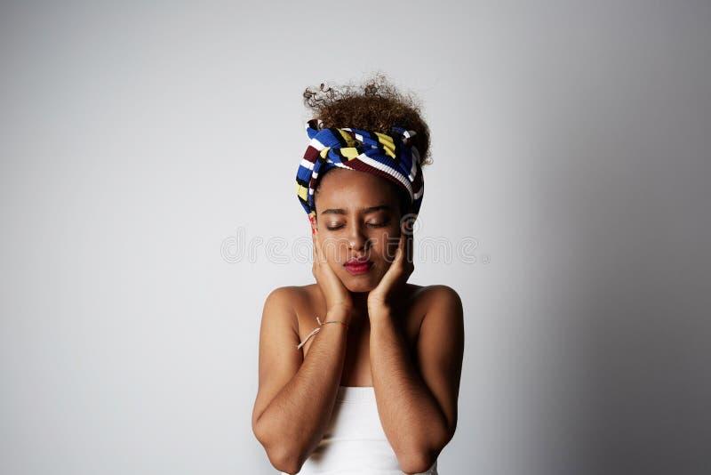 Jong Afrikaans meisje met het krullende kapsel van Afro, die opzij met gesloten die ogen stellen, over helder licht worden ge?sol royalty-vrije stock foto