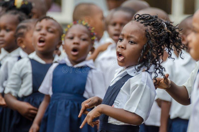 Jong Afrikaans schoolmeisje met prachtig verfraaid haar die en bij pre-school in Matadi, de Kongo, Afrika zingen dansen royalty-vrije stock afbeelding