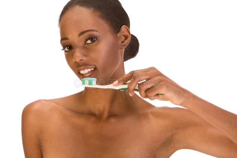 Jong Amerikaans meisje Afro die haar tanden borstelt stock foto's