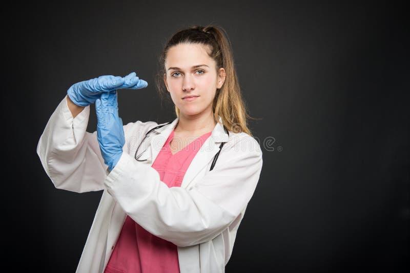 Jong artsenportret die robe dragen die tijd uit gebaar tonen stock foto