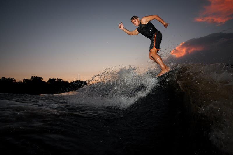 Jong atletisch personenvervoer op wakeboard op de roze zonsondergang stock afbeelding