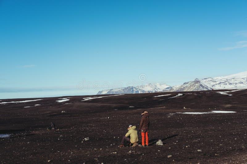 Jong avontuurlijk paar die een onderbreking nemen terwijl het reizen in IJsland bij wintertijd Het concept van de paarlevensstijl stock foto