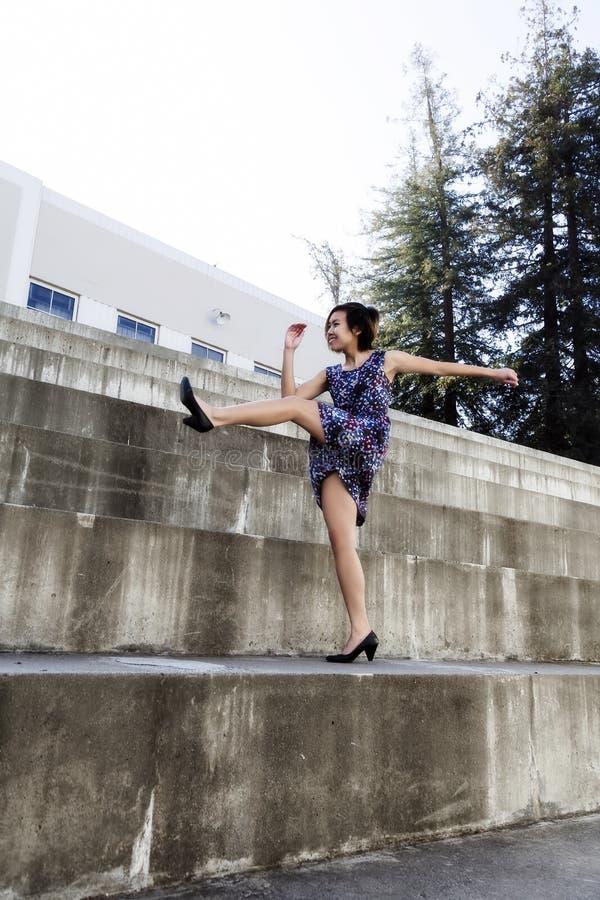 Jong Aziatisch Amerikaans Vrouw het Schoppen Been omhoog in Kleding in openlucht royalty-vrije stock afbeeldingen