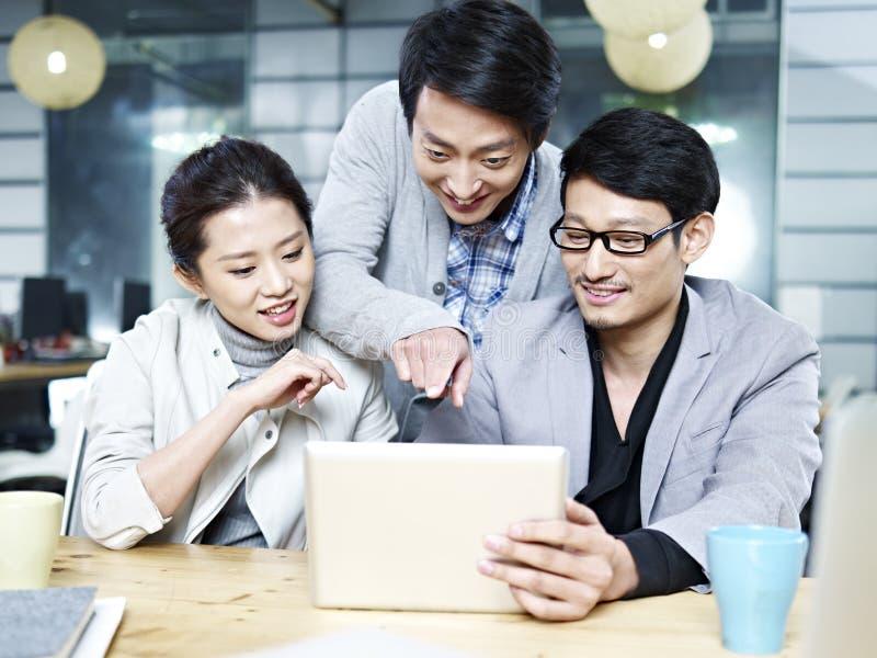 Jong Aziatisch commercieel team die in bureau samenwerken stock afbeeldingen
