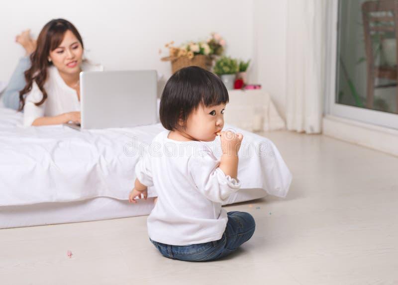 Jong Aziatisch mamma die terwijl haar zitting van het babymeisje aan vloer werken bij stock fotografie