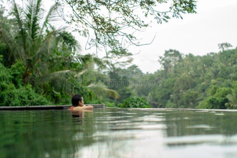 Jong Aziatisch Meisje dat in de oneindigheidspool zwemt met mooie mening royalty-vrije stock afbeeldingen