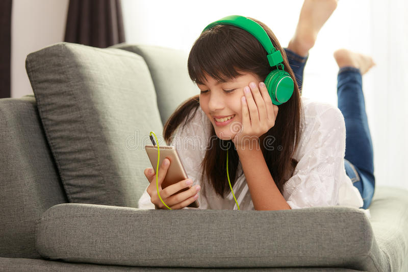 Jong Aziatisch meisje die aan muziek met hoofdtelefoon en smarthpho luisteren stock afbeeldingen