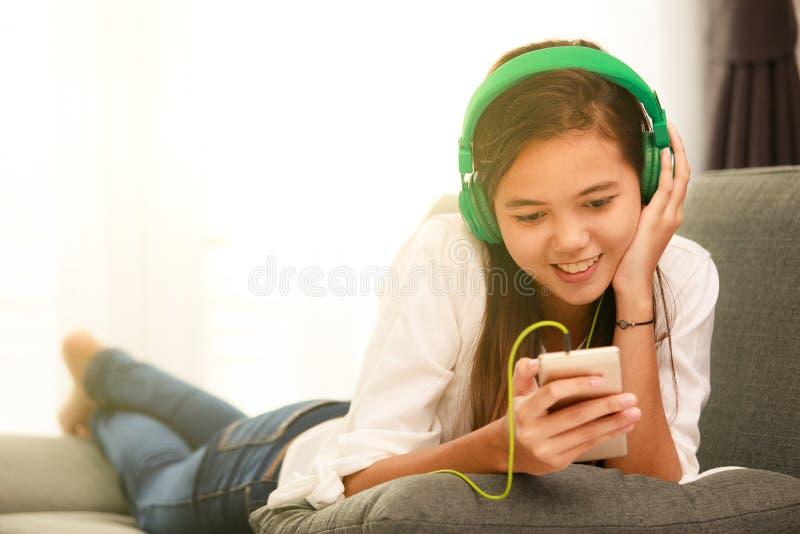 Jong Aziatisch meisje die aan muziek met hoofdtelefoon en smarthpho luisteren royalty-vrije stock fotografie