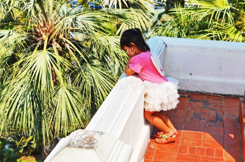 Jong Aziatisch meisje die aangezien zij over een muur staart denken stock afbeelding