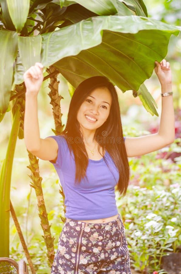 Jong Aziatisch meisje die zich onder het blad bevinden royalty-vrije stock afbeelding