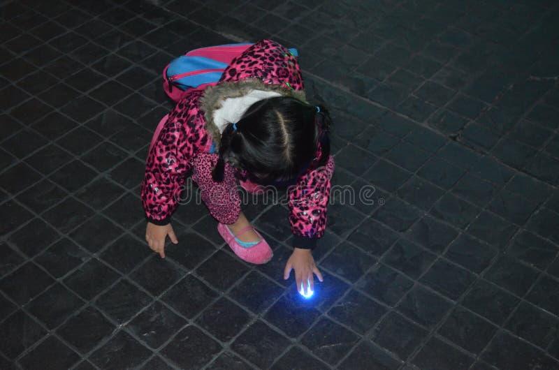 Jong Aziatisch meisje nieuwsgierig over licht in de vloer royalty-vrije stock foto's