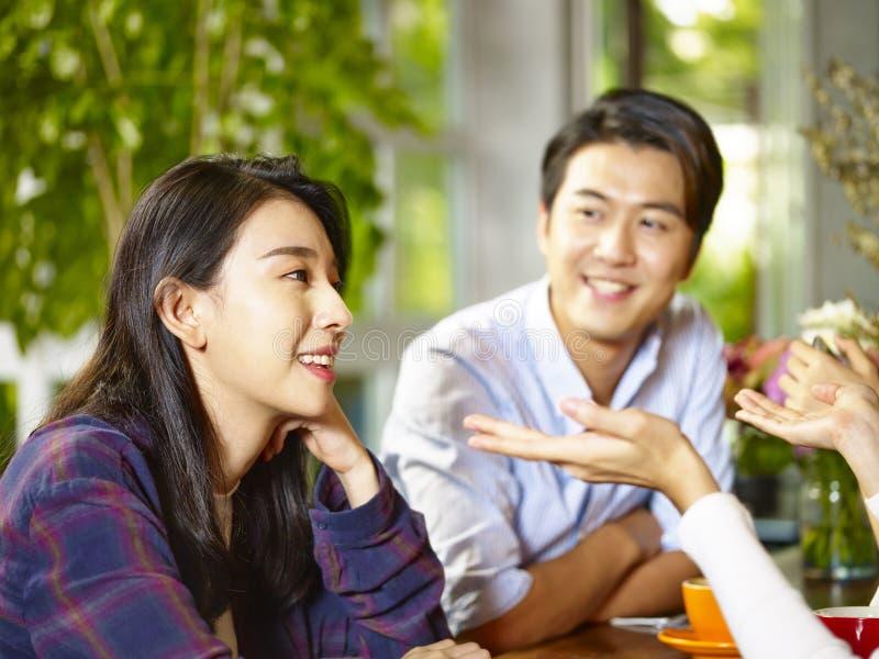 Jong Aziatisch paar die aan vrienden in koffiewinkel spreken stock fotografie