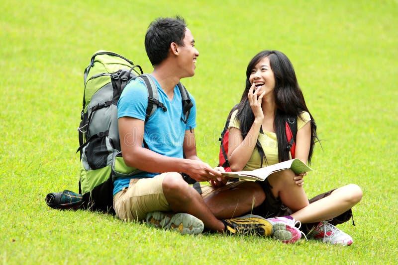 Jong Aziatisch paar die en op het gras babbelen zitten stock foto's