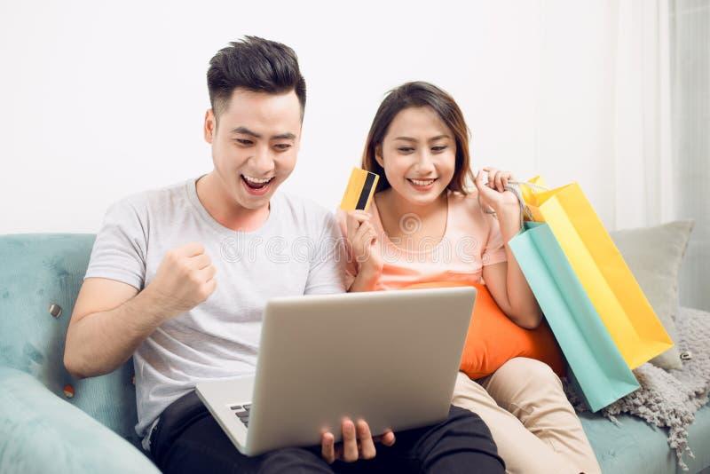 Jong Aziatisch paar die op Internet surfen en met laptop winkelen royalty-vrije stock fotografie