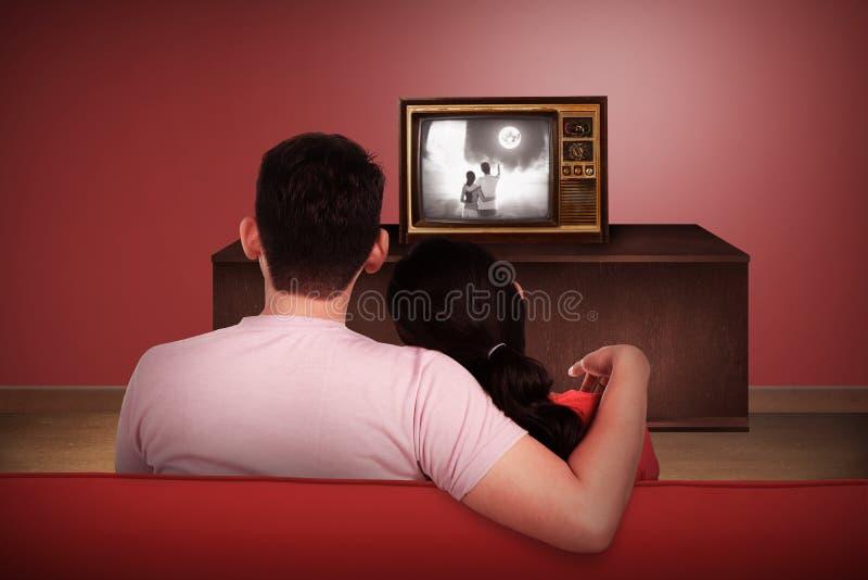 Jong Aziatisch paar die op retro TV letten stock afbeeldingen