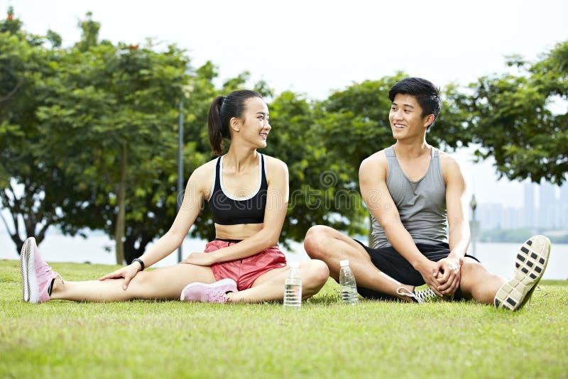 Jong Aziatisch paar die terwijl het uitoefenen spreken stock fotografie