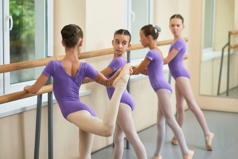 Jong ballerina het uitrekken zich been, achtermening stock fotografie