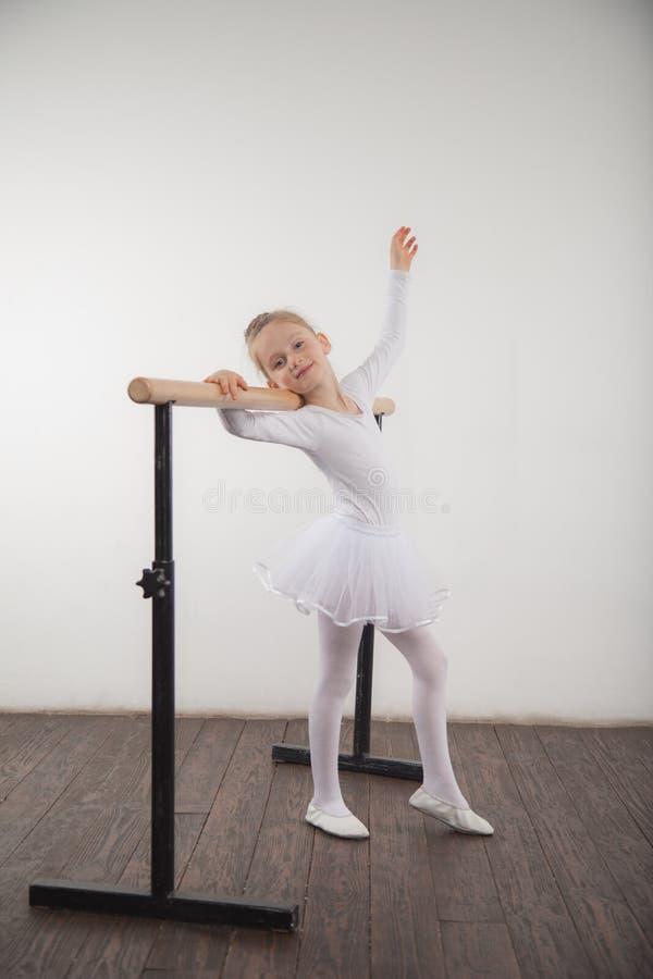 Jong ballerinameisje in een witte tutu Aanbiddelijk kind het dansen klassiek ballet in een witte studio met houten vloer De kinde stock afbeelding