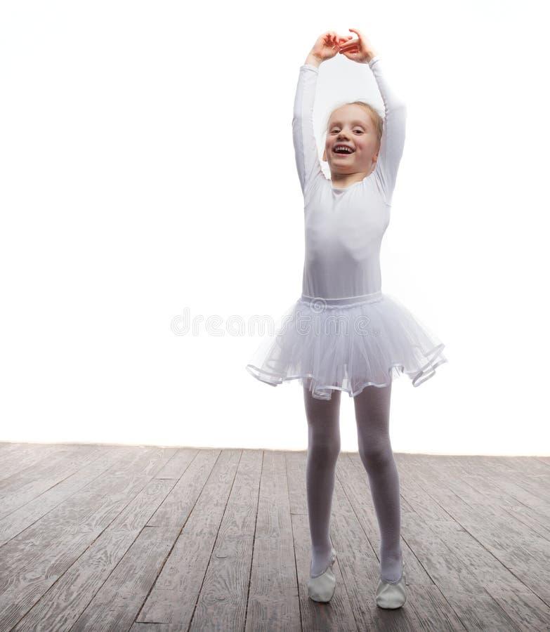 Jong ballerinameisje in een witte tutu Aanbiddelijk kind het dansen klassiek ballet in een witte studio met houten vloer De kinde stock fotografie