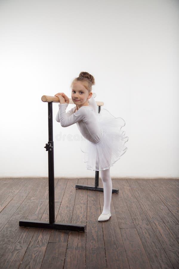 Jong ballerinameisje in een witte tutu Aanbiddelijk kind het dansen klassiek ballet in een witte studio met houten vloer De kinde stock foto