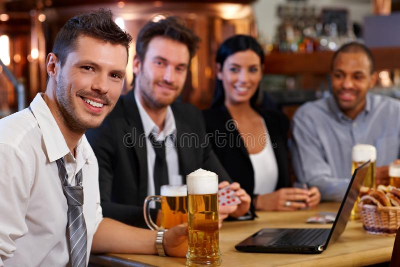 Jong beambte het drinken bier bij bar stock afbeeldingen
