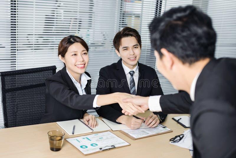 Jong bedrijfsmensenhandenschudden in conferentieruimte royalty-vrije stock afbeeldingen