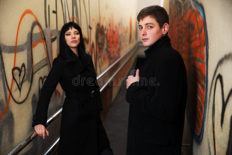 Jong bedrijfspaar bij de muur van de grungegraffiti stock fotografie