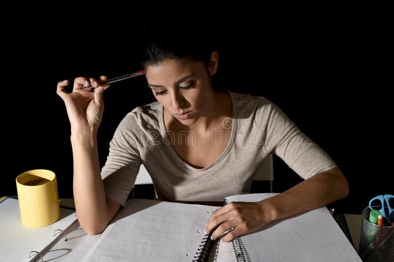 Jong bezig mooi Spaans meisje die thuis laat - nacht die voorbereidend geconcentreerd examen eruit zien bestuderen royalty-vrije stock fotografie