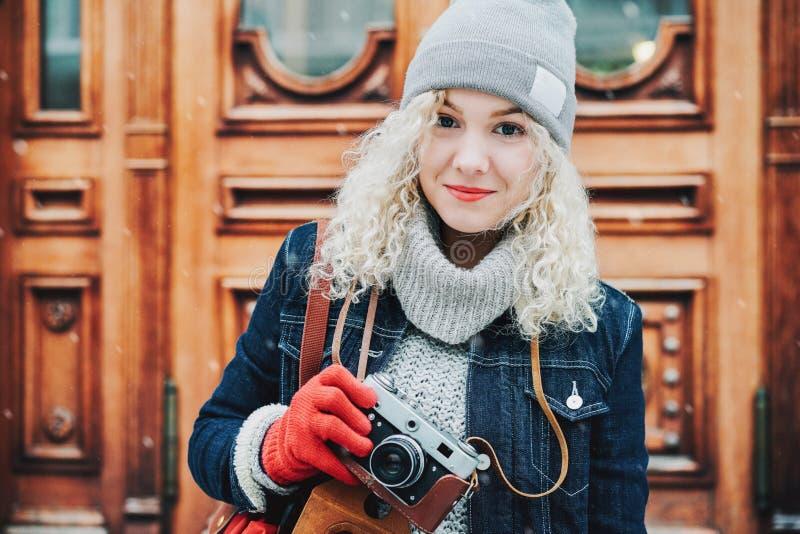 Jong blond krullend meisje met retro filmcamera, de winter stock afbeelding
