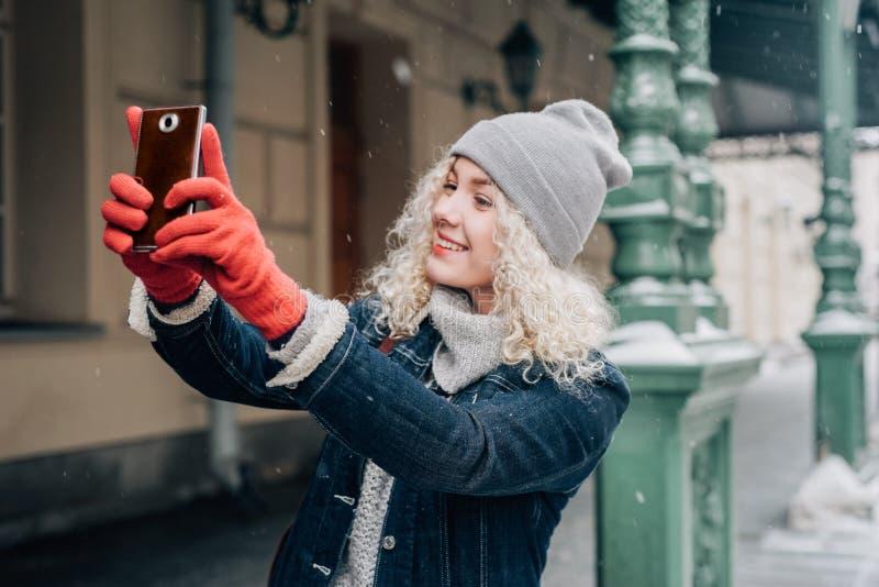 Jong blond krullend toeristenmeisje die in warme kleren selfie maken stock afbeeldingen
