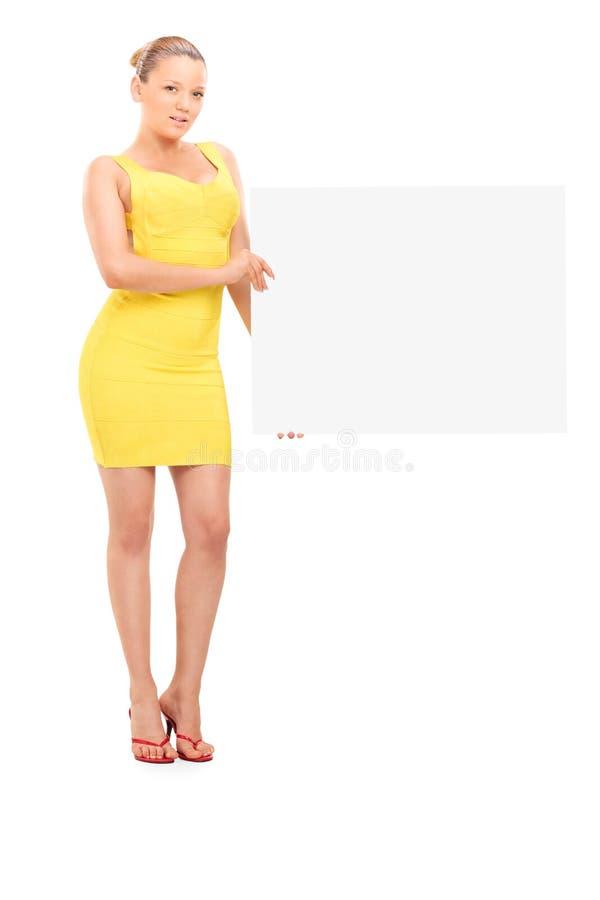 Jong blond meisje die een leeg uithangbord houden stock fotografie