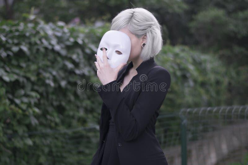 Jong blond meisje die een masker opstijgen Bewerend om te zijn iemand anders concept outdoors royalty-vrije stock fotografie