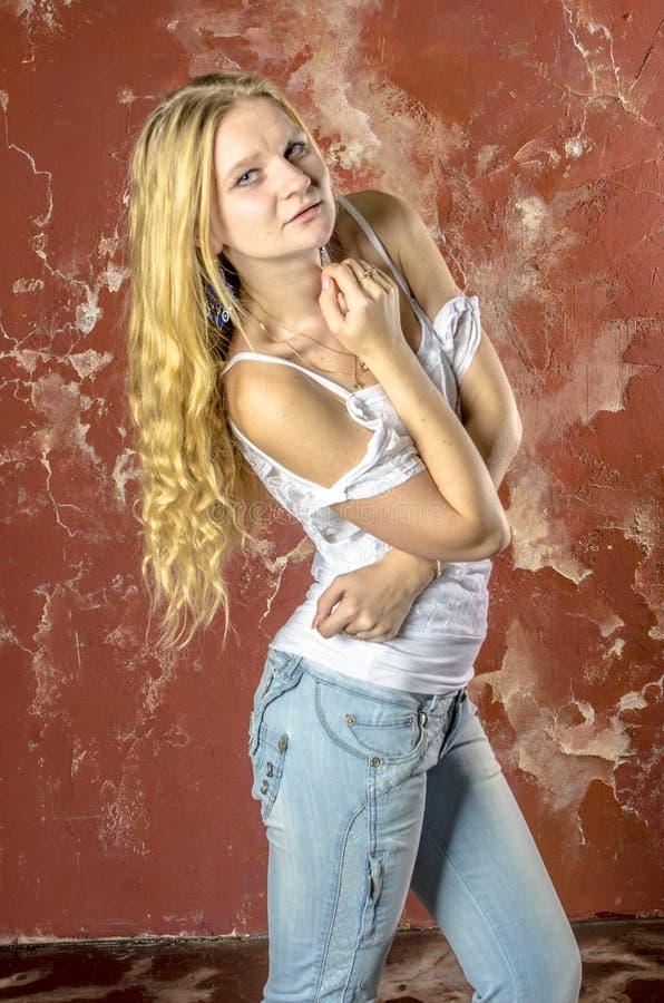 Jong blond meisje in jeans en een witte sweater stock afbeeldingen
