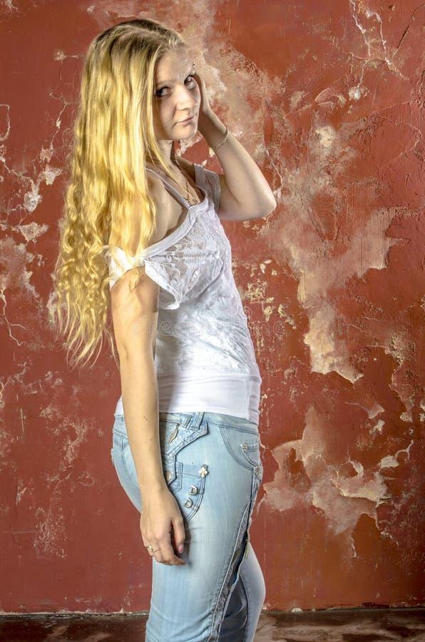 Jong blond meisje in jeans en een witte sweater stock fotografie