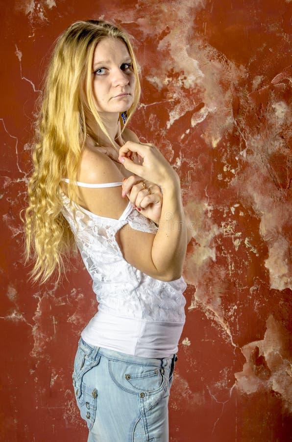 Jong blond meisje in jeans en een witte sweater royalty-vrije stock afbeelding