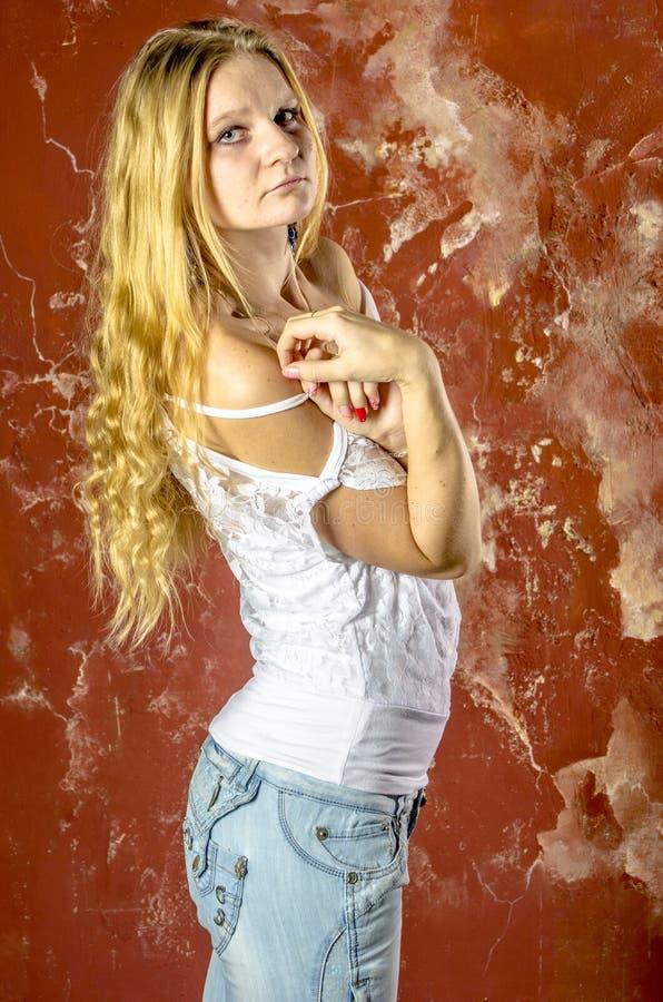 Jong blond meisje in jeans en een witte sweater royalty-vrije stock fotografie